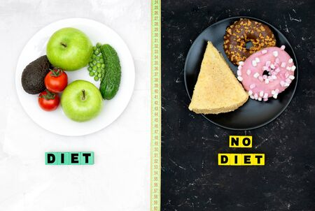 White plate with vegetables and fruits and black plate with donuts and a cake on contrast backgrounds divided with a measuring tape. Dieting extremes and balanced healthy eating concept.