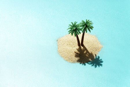 Miniature toy tropical island with palm trees in the ocean. Harsh sunlight effect, copy space. Creative summer vacation concept.
