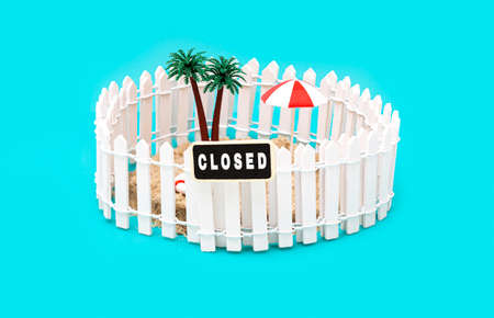 Fenced miniature toy island with palm trees, sun umbrella and a sign saying CLOSED on light blue background. Tourism industry crisis. Banned summer vacations and traveling due to coronavirus pandemic. Foto de archivo