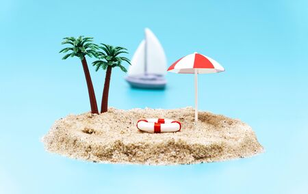 Miniature toy island with palm trees, sun umbrella, a lifebuoy and a sailboat on a light blue background imitating the ocean. Remote island for a tropical getaway.