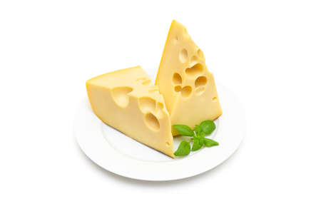 Two wedge-shaped pieces of cheese with large holes and fresh basil on a white plate isolated on white background 写真素材