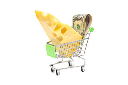Cheese wedge and dollar bills in a miniature shopping cart isolated on white. Shopping savings and grocery deals concept.