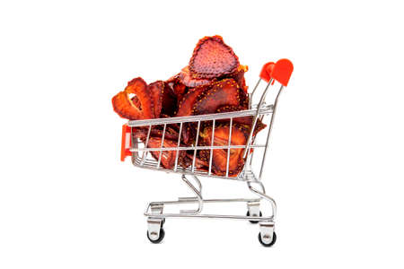 Dehydrated sliced strawberries in a miniature shopping cart isolated on white 版權商用圖片