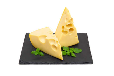 Two wedges of fresh cheese and basil leaves on a black stone board isolated on white background