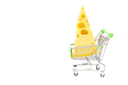 Big holes cheese wedge in a miniature shopping cart isolated on white. Online shopping and fresh groceries delivery concept.