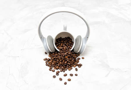 Wireless overhead headphones on a coffee cup and roasted coffee beans scattered on a textured concrete table