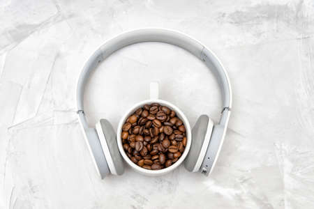 Wireless headphones on a porcelain cup full of roasted coffee beans on a concrete table 版權商用圖片