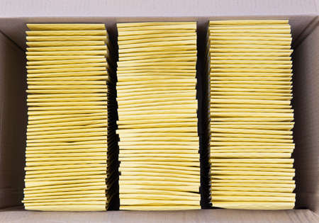 Top view of three stacks of yellow mail envelopes neatly packed in a large shipping box