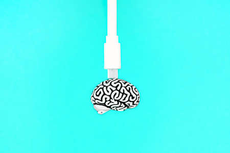 White data cable attached to a small steel copy of a human brain isolated on a blue background. Creative education and knowledge transfer concept.