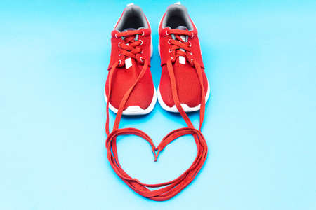 Red athletic sneakers and a heart symbol made of shoelaces on a blue background. Running passion romantic concept.