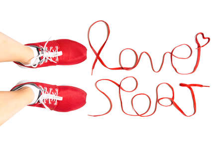 "Cropped view of female feet wearing red running sneakers and lettering ""love sport"" made of athletic shoelaces isolated on white background. Active lifestyle concept."