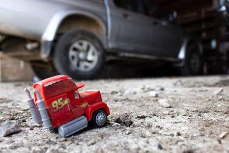 modellino di un camion abbandonato sul marciapiede sullo sfondo di un vecchio e sporco pickup Archivio Fotografico