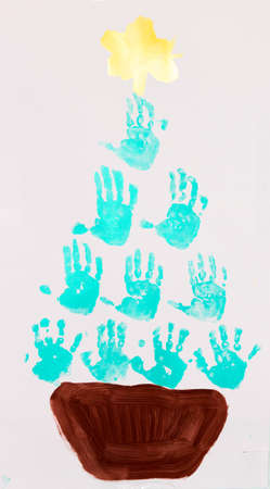 Christmas tree painted with children's handprints in colorful paint.