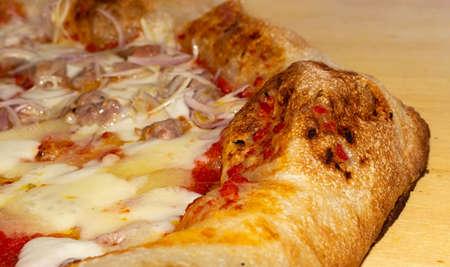 closeup of soft pizza topped with tomato mozzarella salami sausage onion