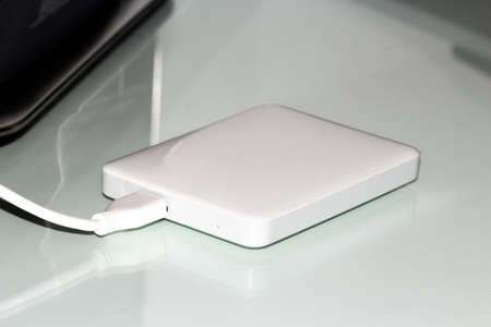 white external hard disk connected with usb cable to the pc resting on the desk.