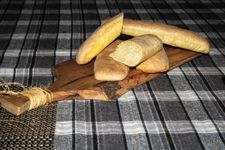 Baked golden bread loaf on a wooden chopping board.