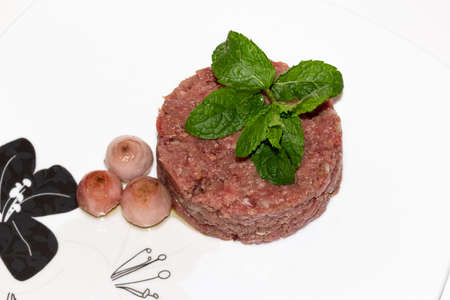 fresh beef tartar dish with tasty onion and with mint leaves.