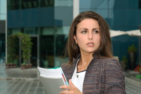 indignant: Business woman with a folder in her hands strongly indignant against the backdrop of the city Stock Photo