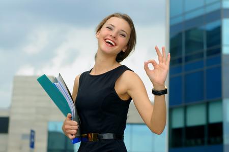 Business-Frau mit einem Ordner in der Hand zeigt, dass alles in Ordnung ist und Spaß lacht vor dem Hintergrund der modernen Gebäudefassaden Standard-Bild