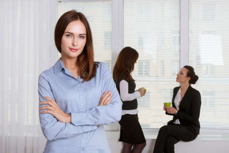 Girl in formal attire is standing in the foreground, and her colleagues have a talking in the background Stock Photo