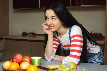listens: Brunette housewife wearing in blue denim overalls enthusiastically listens to someone. Girl looking slightly to the side and rests his hand on the table.