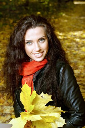 Beautiful girl sitting on yellow leaves in autumn park