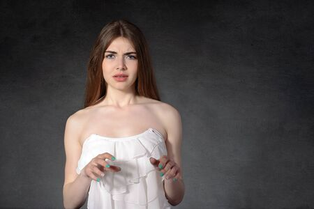 unhappy people: Concept human emotions. Girl showing disgust against a dark background