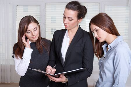 studygroup: Three women are studying the information in a folder