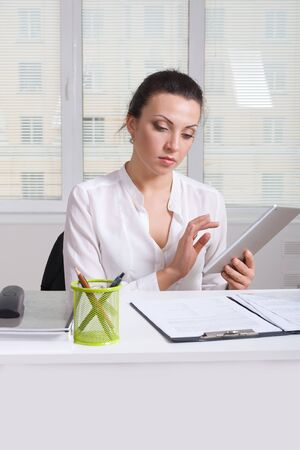 formal shirt: Girl in white formal shirt holding a a tablet browsing news