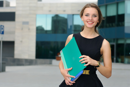 Woman walking on business district with folders in her hands and smiling