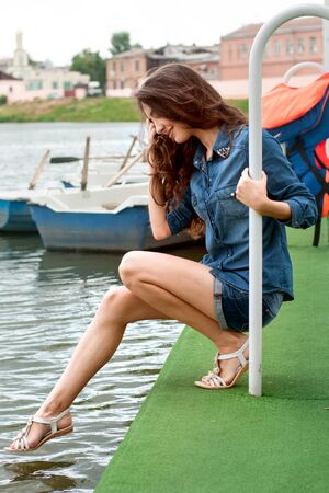 omitted: Girl puts her foot into the water holding on to the railing on the boat station