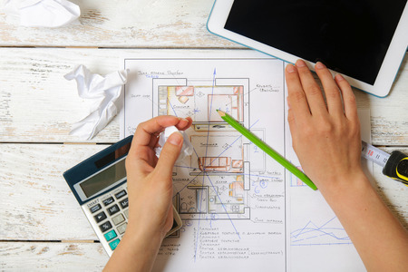 Girl draws a plan of Feng Shui for the home using the calculator and tablet. Top view Stock Photo