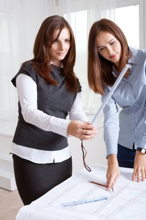 dimensions: Two female architects studying blueprints and other one shows the dimensions of on the ruler