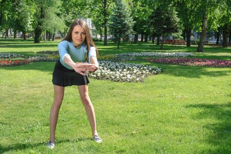 leaning forward: Girl doing exercise leaning forward on a green grass in the park