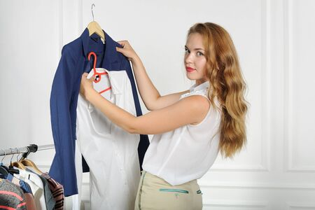 comparing: Woman chooses clothes in a clothing store comparing things with each other against the light background