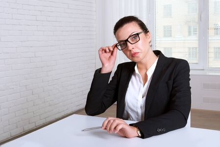 disdain: Woman in suit looking disdainfully lifting eye glasses Stock Photo