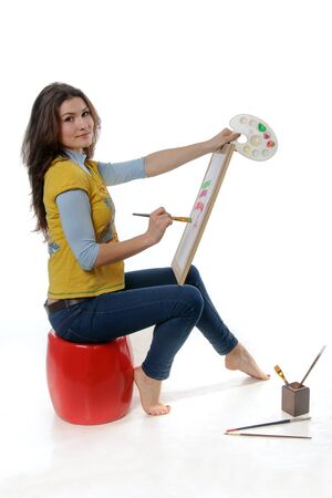 Woman artist sitting sideways to the camera holding an easel, palette and brush against an isolated background.