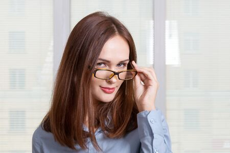 formal attire: Girl in formal attire looking over his glasses at the camera Stock Photo