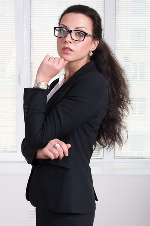 hand on the chin: Woman leader in black business suit and glasses standing turned aside and propping up her hand chin