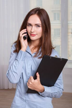 formal attire: Girl in formal attire holding a folder and speaks by phone