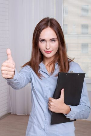 formal attire: Girl in formal attire holding a folder and gesture shows that everything is OK