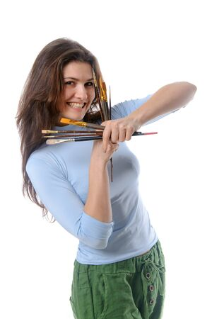 both: Girl artist stands in half-turn holding her brushes with both hands and smiling on isolated background