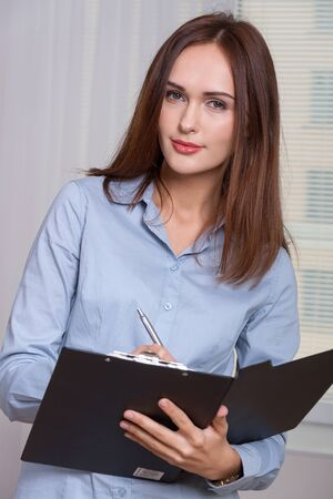 formal attire: Woman in formal attire opened the folder for documents and writes it