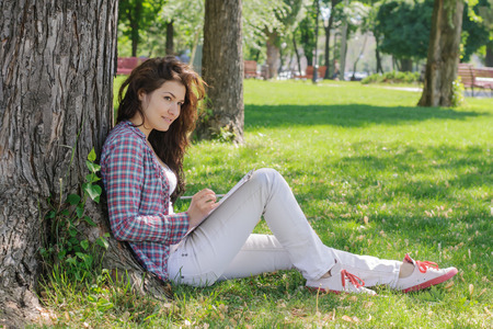 writing paper: The girl draws sketches on paper sitting on the grass in the park Stock Photo