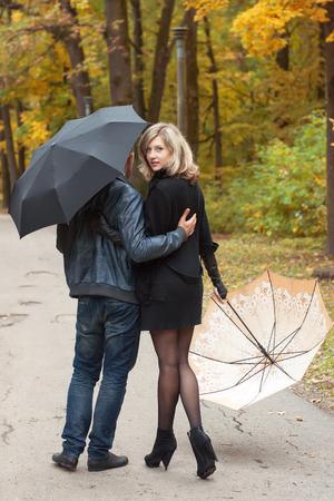 UOMO pioggia: Uomo e la donna a piedi sotto gli ombrelli in autunno parco