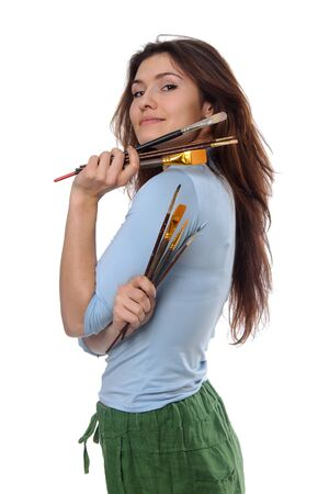 proudly: Woman artist holding her brushes in each hand and looking over her shoulder proudly against an isolated background Stock Photo