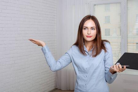 formal attire: Woman in formal attire holding a folder expressing bewilderment Stock Photo