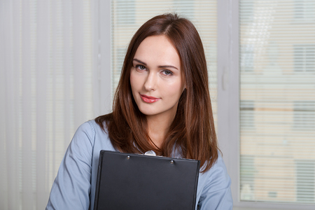 formal attire: Woman in formal attire holding a folder for documents