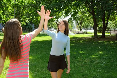 Two girls say goodbye after exercise outdoors at park against the backdrop of greenery