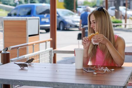 flew: Girl sitting in an outdoor cafe and feeding the birds flew crumbs